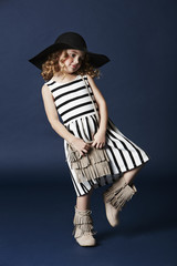 Fashionable girl posing in striped dress