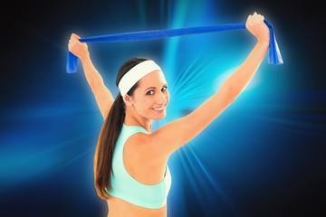Composite image of fit young woman holding up a blue yoga belt