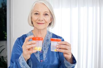 Senior Woman Holding Pill Bottles At Nursing Home