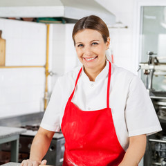 Portrait Of Happy Female Chef In Red Apron