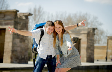 American student tourist couple taking selfie photo with stick