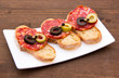 Bruschetta with salami and olives on wooden table