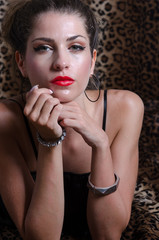 Sexy woman in studio, animal print fabric as background