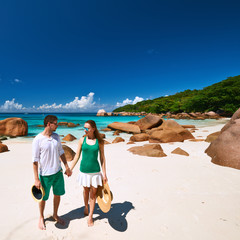 Couple in green walking on a beach at Seychelles