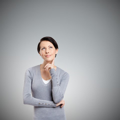 Pensive woman, isolated on grey background
