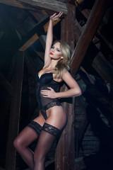 Sensual woman in black underwear posing in barn