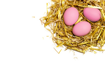 pink eggs in a nest of straw isolated on white background