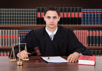 Confident Male Judge Sitting In Courtroom