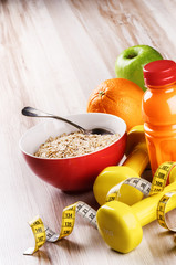 Fitness concept with dumbbells, oatmeal and fresh fruits