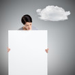 Woman brings a huge sheet of white cardboard, isolated on grey
