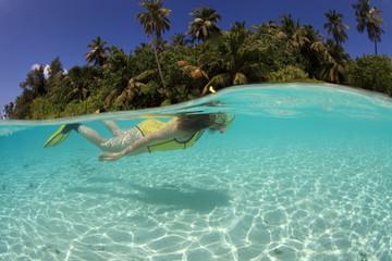 Female snorkeler diving in blue lagoon