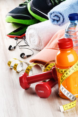 Fitness concept with dumbbells, fruits juice and sportswear
