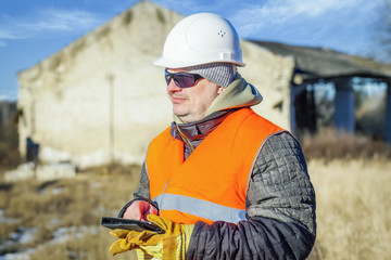 Engineer with tablet PC near destroyed building in winter