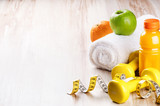 Fitness concept with dumbbells and fresh fruits