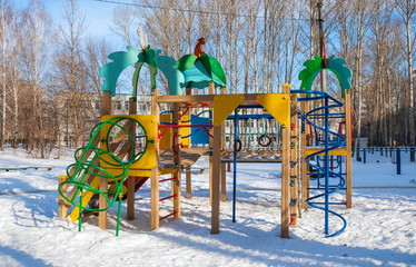 Playground with climbing frame and slides in  winter yard