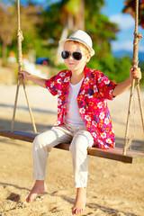cute stylish boy on swings at the beach