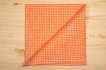 Folded orange-white napkin on wooden table