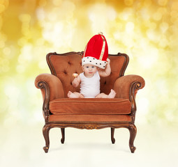 baby in royal hat with lollipop sitting on chair