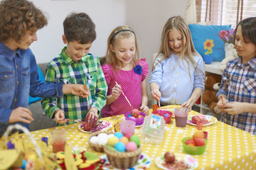 Group of little friends have fun with painting Easter eggs