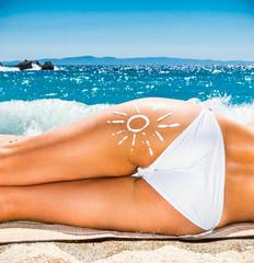 Hot beautiful woman with suntan loton sign on the beach.