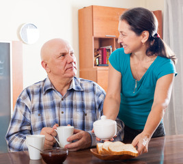 mature woman serving tea for her  man