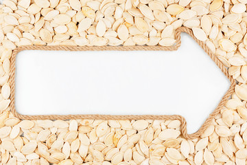 Arrow made of rope with pumpkin seeds  with a white background