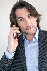 man in a checkered suit talking on cell phone