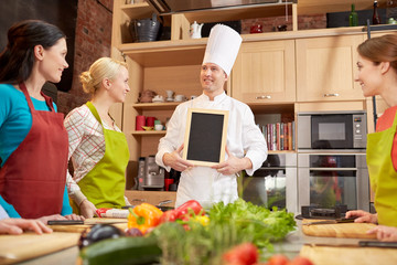 happy women and chef cook with menu in kitchen