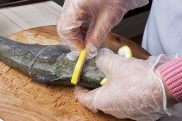Woman-cook cooking trout with lemon at cuisine