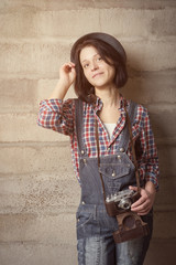 Indoor portrait of woman in a hipster style with vintage camera