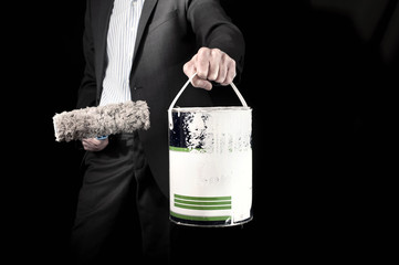 Businessman with suit holding paint roller and a bucket of paint