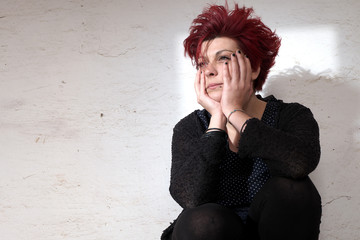 Desperate woman sitting against white wall