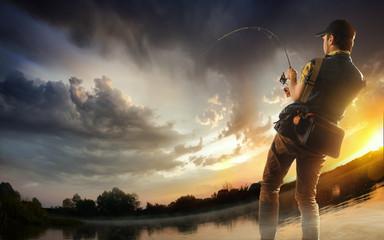 Young man fishing at dramatic sunset
