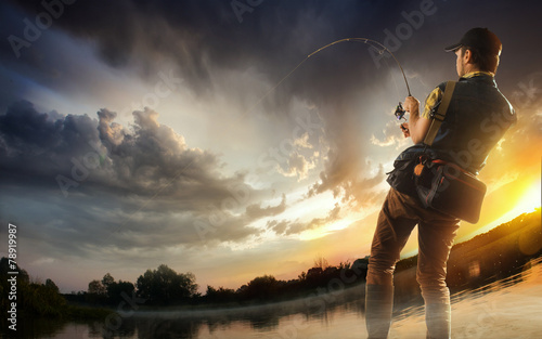 Tuinposter Vissen Young man fishing at dramatic sunset