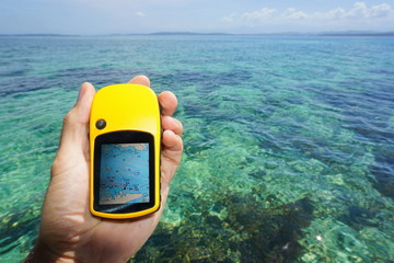 Hand holding a marine GPS navigator over the sea