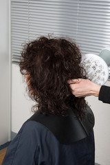 Stylist blow drying hair of a client at the beauty salon