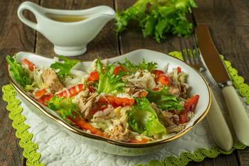 Salad with tuna and red pepper on a wooden table