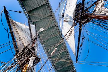 Tall ship sailboat passing under a bridge. View looking up