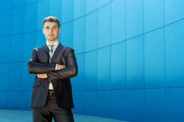 Portrait of young handsome successful business man in suit stand