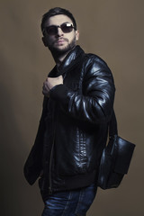 Fashion portrait of handsome young man in trendy casual leather