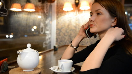 Young girl talking on the phone in an evening bar, restaurant, c