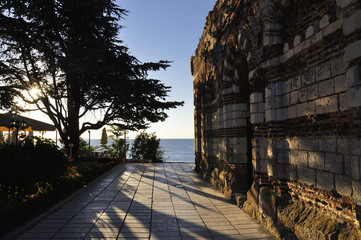Street of old town Nesebar filled in with light of sunrise