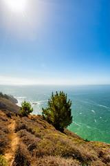 California coastal cliff trail with ocean view. Sun flare