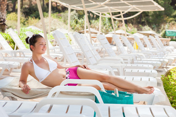Woman In Swimwear Relaxing On Lounge Chair At Resort