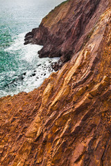 Colorful rocky steep cliffs over the Pacific Ocean