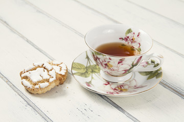 A tea cup with shortbread on a white table. Vintage Style.