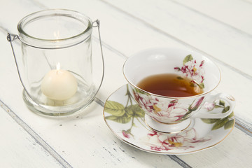 A tea cup with a candle on a white wooden table. Vintage Style.