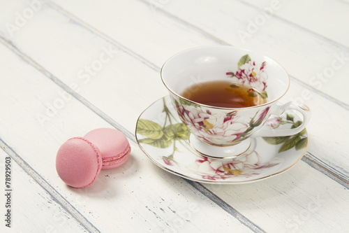 Plexiglas Thee A tea cup with two macarons (macaroon) on a table. Vintage Style