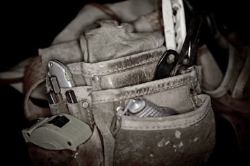 Rugged worn leather carpenters work bags with construction tools