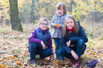 Happy Siblings - Three sisters in the autumnal forest smiling